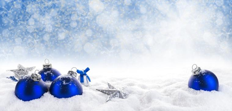 Blaue Weihnachtskugeln, ein Glöckchen und Sterne im Schnee vor sonnigem Bokehhimmel, Panorama